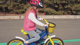 Peque?a bici rubia de cinco a?os del montar a caballo de la muchacha en un parque viejo almacen de metraje de vídeo