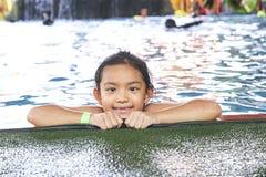 Peque?a muchacha asi?tica feliz en la piscina imagen de archivo libre de regalías