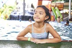 Peque?a muchacha asi?tica feliz en la piscina foto de archivo libre de regalías