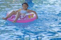 Peque?a muchacha asi?tica feliz en la piscina imagenes de archivo