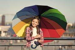 Peque?a muchacha bonita que se coloca con el paraguas colorido Muchacha en el puente Ocultaci?n del sol con el paraguas Sombras b foto de archivo libre de regalías