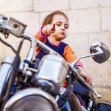 Peque?a muchacha fresca del motorista que juega y que se divierte en la motocicleta formada Retrato chistoso de los puntos del ni fotografía de archivo libre de regalías