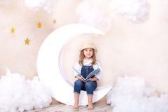 Peque?a muchacha linda que se sienta en la luna con las nubes y las estrellas con un libro en sus manos y lectura La muchacha est foto de archivo
