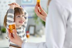Peque?a muchacha paciente linda que se divierte que selecciona una botella de medicaciones imágenes de archivo libres de regalías