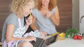 Peque?a muchacha rizada en el delantal que se sienta en la tabla y que usa el ordenador port?til y a su madre que cocinan cerca e almacen de metraje de vídeo