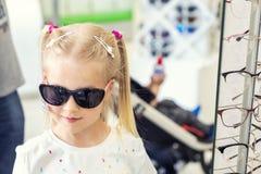 Peque?a muchacha rubia cauc?sica joven linda que intenta encendido y que elige las gafas de sol delante del espejo en la tienda ? foto de archivo libre de regalías
