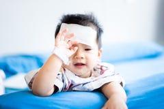 Peque?o beb? asi?tico enfermo con el coj?n fresco del jel de la fiebre en la frente imagenes de archivo