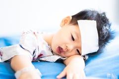 Peque?o beb? asi?tico enfermo con el coj?n fresco del jel de la fiebre en la frente fotos de archivo
