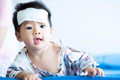 Peque?o beb? asi?tico enfermo con el coj?n fresco del jel de la fiebre en la frente fotografía de archivo libre de regalías