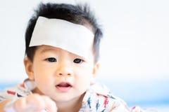 Peque?o beb? asi?tico infeliz enfermo con el coj?n fresco del jel de la fiebre en la frente fotografía de archivo libre de regalías