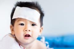 Peque?o beb? asi?tico infeliz enfermo con el coj?n fresco del jel de la fiebre en la frente fotografía de archivo