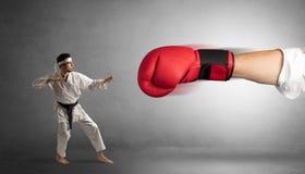 Peque?o hombre que lucha con el guante de boxeo rojo grande foto de archivo