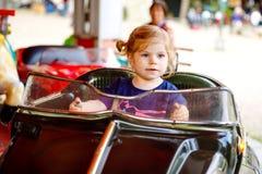 Peque?o montar a caballo adorable de la ni?a peque?a en el coche divertido en el carrusel del cruce giratorio en parque de atracc imagenes de archivo