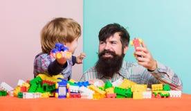 peque?o muchacho con el pap? que juega junto Desarrollo infantil Ocio feliz de la familia hogar del edificio con el constructor c foto de archivo