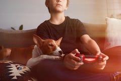 Peque?o muchacho lindo que juega la consola del videojuego asentada en un sof? con cierre del perrito del perro del basenji en sa fotografía de archivo