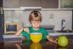 Peque?o muchacho rubio feliz del ni?o que come los cereales para el desayuno o el almuerzo Consumici?n sana para los ni?os Ni?o q imagen de archivo libre de regalías