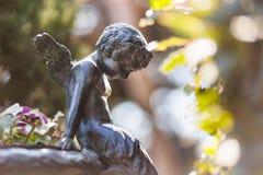 Peque?o ?ngel de la estatua en backgorund del parque natural imagen de archivo