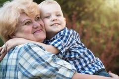 Peque?o nieto que abraza a la abuela que se sienta en sus brazos D?a de fiesta de la familia al aire libre fotografía de archivo