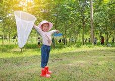 Peque?o sombrero de paja asi?tico adorable del desgaste de la muchacha en un campo con la red del insecto en verano Actividad al  foto de archivo
