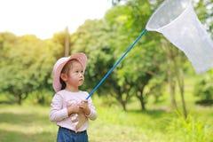 Peque?o sombrero de paja asi?tico adorable del desgaste de la muchacha en un campo con la red del insecto en verano Actividad al  fotos de archivo