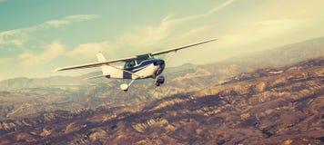 Peque?o vuelo del aeroplano del solo motor en el cielo magn?fico de la puesta del sol a trav?s del mar de nubes sobre las monta?a imágenes de archivo libres de regalías