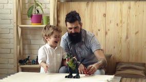 Peque?os juegos de ni?os adorables con su padre barbudo con los dinosaurios pl?sticos Juego del hijo y del padre en lucha de la b almacen de video