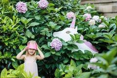 Peque?a princesa con unicornio del juguete Una peque?a princesa feliz utiliza su imaginaci?n para presentar con su unicornio del  imagen de archivo