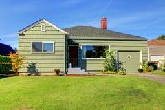 Pequeña casa verde verde con la puerta del garaje. Fotos de archivo libres de regalías