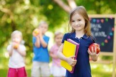 Pequeña colegiala emocionada que vuelve a la escuela Imágenes de archivo libres de regalías