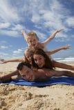 Pequeña familia que miente en la playa Imagen de archivo libre de regalías