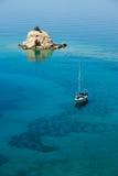 Pequeña isla solitaria y barco de navegación Imagen de archivo libre de regalías