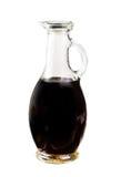 Pequeña jarra con el vinagre balsámico aislado en el fondo blanco Imagen de archivo