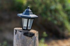 Pequeña lámpara solar en la madera Imagenes de archivo