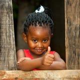 Pequeña muchacha africana en la cerca de madera con los pulgares para arriba. Imagen de archivo libre de regalías