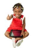 Pequeña muchacha afroamericana que usa la PC de la tableta Imagen de archivo