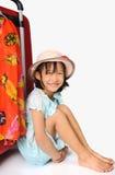 Pequeña muchacha asiática en el sombrero de la armadura que se sienta cerca de un viaje enorme su rojo Foto de archivo libre de regalías