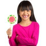 Pequeña muchacha asiática feliz y dientes quebrados que sostienen una piruleta Imágenes de archivo libres de regalías