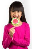 Pequeña muchacha asiática feliz y dientes quebrados que sostienen una piruleta Imagenes de archivo