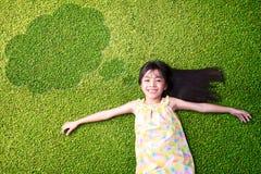 Pequeña muchacha asiática que descansa sobre hierba verde Imagen de archivo libre de regalías