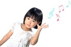 Pequeña muchacha asiática que escucha la música en la naturaleza Fotos de archivo