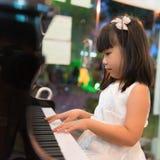 Pequeña muchacha asiática que juega el piano Foto de archivo libre de regalías