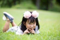 Pequeña muchacha asiática que juega en hierba verde en el parque Imagen de archivo libre de regalías