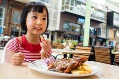 Pequeña muchacha china asiática que come la comida occidental Fotos de archivo