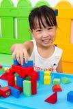 Pequeña muchacha china asiática que juega bloques de madera Imagen de archivo libre de regalías