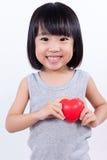 Pequeña muchacha china asiática que lleva a cabo el corazón rojo Imagen de archivo libre de regalías