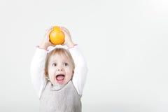 Pequeña muchacha de griterío con la naranja Imagen de archivo libre de regalías