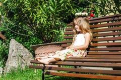 Pequeña muchacha descalza linda que se sienta en el banco Imágenes de archivo libres de regalías