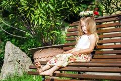 Pequeña muchacha descalza linda que se sienta en el banco Foto de archivo libre de regalías