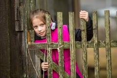 Pequeña muchacha linda que se coloca detrás de una cerca en el pueblo Imagen de archivo