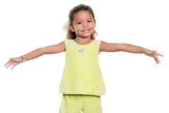 Pequeña muchacha que sonríe con sus brazos abiertos de par en par Foto de archivo libre de regalías